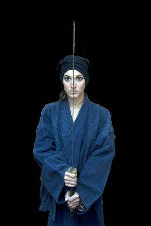 Portrait of a beautiful woman with japanese clothing wielding a katana photo