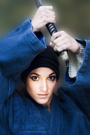 Portrait of a beautiful woman with japanese clothing wielding a katana Stock Photo - 17471806