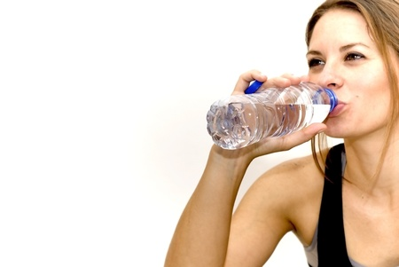 Beautiful woman drinking water after playing sports on white background