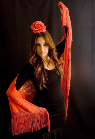 Beautiful woman with typical dress of flamenco in Spain on black background