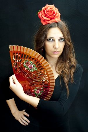 Beautiful woman with typical dress of flamenco in Spain on black background photo