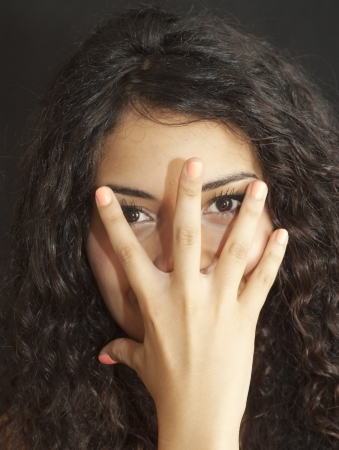 Portrait of an attractive woman, with hand on face, on black background