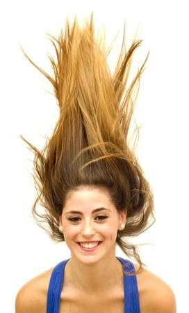 Retrato de uma jovem mulher com camisa azul e os cabelos ao vento sobre o fundo branco