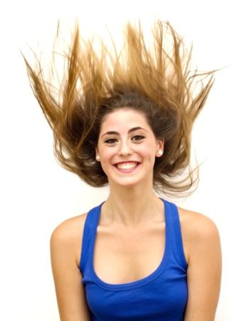 Retrato de uma mulher jovem com camisa azul e os cabelos ao vento sobre o fundo branco