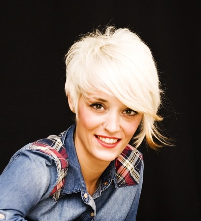 Beautiful woman with denim shirt and short white hair on black background Stock Photo