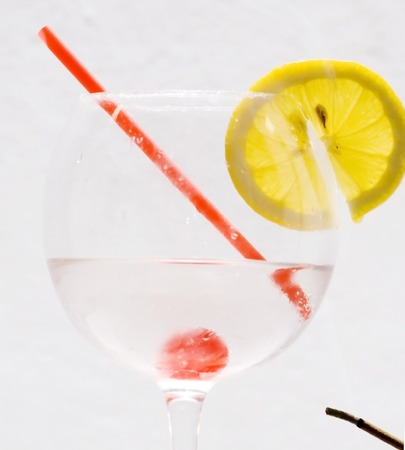 Cocktail with lemon slice, cherry and a straw photo