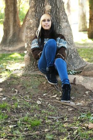 Menina latin bonita em um parque no outono encostado a uma