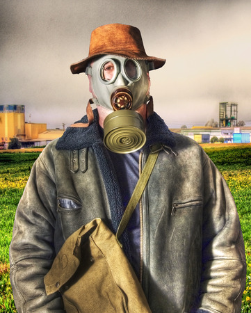 Man with a gas mask and background factories and pollution photo