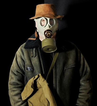 Man with a gas mask over black background photo