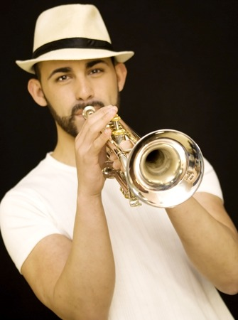 handsome guy playing a trumpet with beard and hat and  on black background