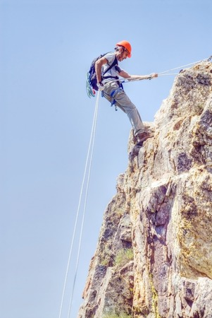 Climber rappelling making a vertical mountain wall  photo