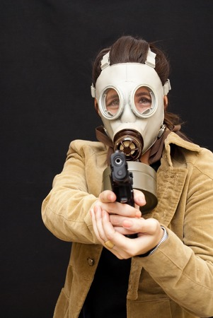 Portrait of Beautiful Young Woman  With Jacket, Gas Mask And Gun Over Black Background photo