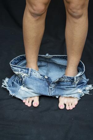 pantalones abajo: Retrato de atractiva joven Womanwith sus pantalones hacia abajo sobre fondo Negro