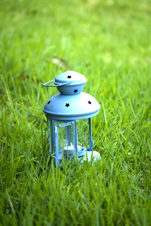 obscura: Blue Lantern, with unlit candle inside, on green grass - stock image