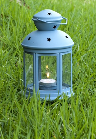 obscura: Blue Lantern, with burning candle inside, on green grass - stock image