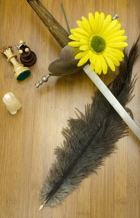 Ancient sword, a candle, a yellow flower, two pieces of chess and former pen writing on a wooden table photo