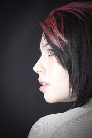 hair tuft: Portrait of Beautiful Young Woman with a red tuft Over Black Background