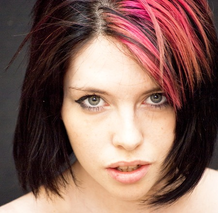tuft: Portrait of Beautiful Young Woman with a red tuft Over Black Background