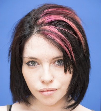 tuft: Portrait of Beautiful Young Woman with a red tuft Over Blue Background