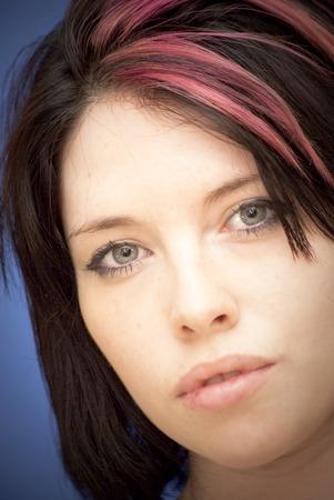 Retrato da mulher nova bonita com um topete vermelho sobre o fundo azul