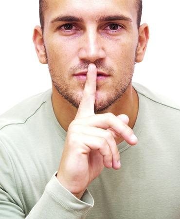 commanding: Handsome man commanding silence over white background
