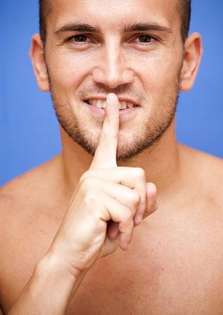 shushing: Handsome man shirtless shushing over blue background