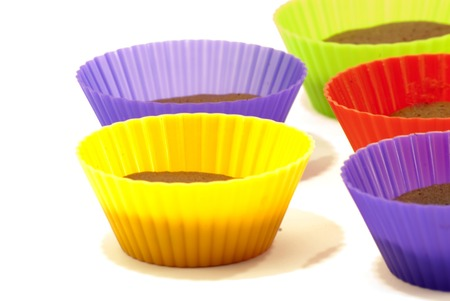 Chocolate muffins in silicone holders of many colors on white background photo