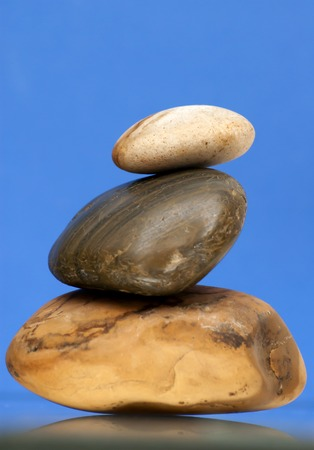 piled: Three Piled Stones on a Mirror  over blue background.