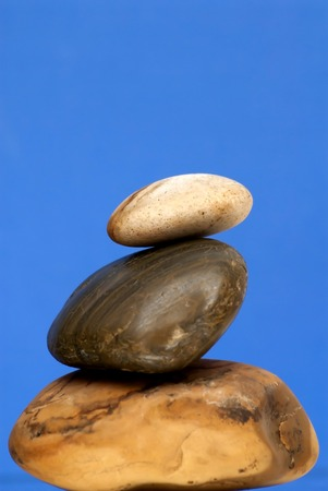 piled: Three Piled Stones over blue background.