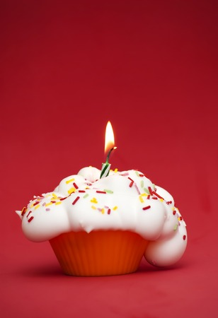 lit: Cupcake with a lit candle over red background