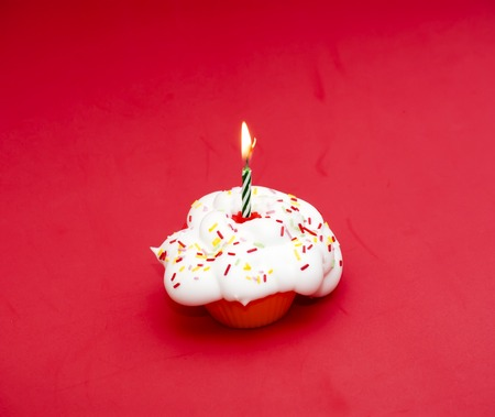 lit candle: Cupcake with a lit candle over red background