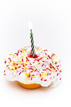 lit: Cupcake with a lit candle over white background