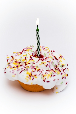 lit candle: Cupcake with a lit candle over white background