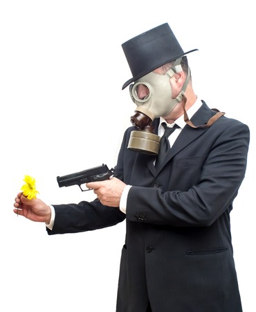 catastrophe: Businessman with gas mask and with a hat that is pointing with a gun to a flower over white