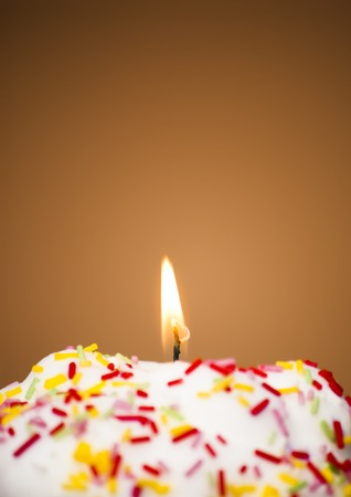 lit: Cupcake with a lit candle  in an moody atmosphere