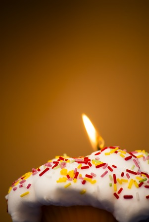 lit candle: Cupcake with a lit candle  in an moody atmosphere