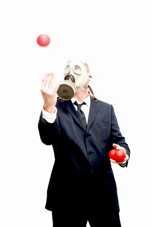 catastrophe: Businessman with gas mask  that is juggling with a red balls over white