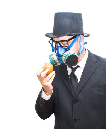 mania: Businessman with gas mask and hat looking at an apple in His hand over white