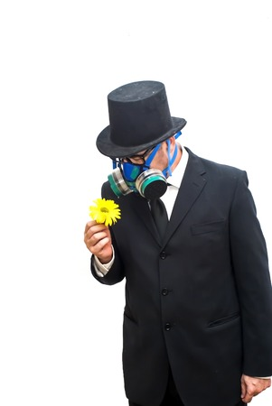 mania: Businessman with gas mask and hat looking at an flower in his hand over white