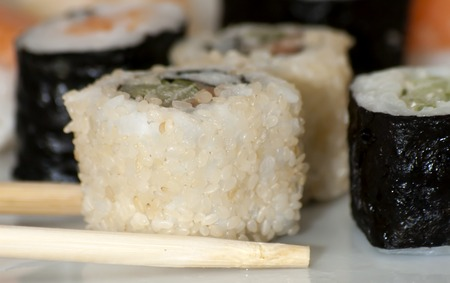 finesse: Different japanase sushi rolls on white plate with chopstic Stock Photo