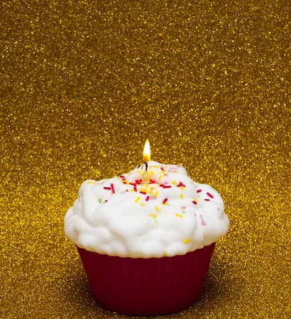 lit candle: Cupcake with a lit candle over bright background
