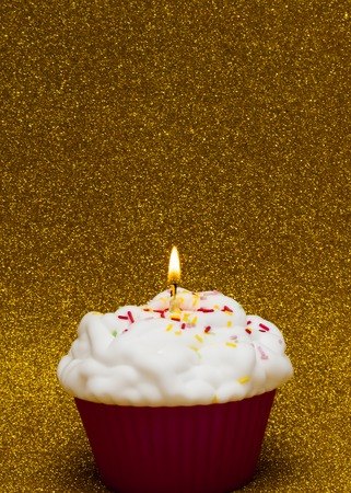 christmas paste: Cupcake with a lit candle over bright background