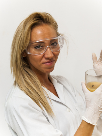 hectic: Beautiful woman doctor, with special glasses,  investigating a sample in a test tube on white background