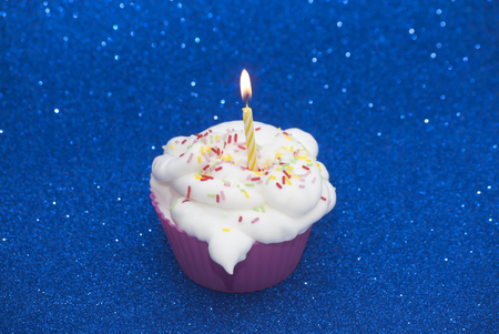 lit candle: Cupcake with a lit candle over bright blue background
