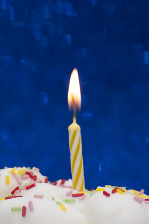 lit: Cupcake with a lit candle over bright blue background