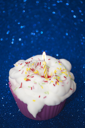 christmas paste: Cupcake with a lit candle over bright blue background