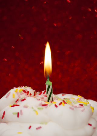 lit: Cupcake with a lit candle over bright red background Stock Photo