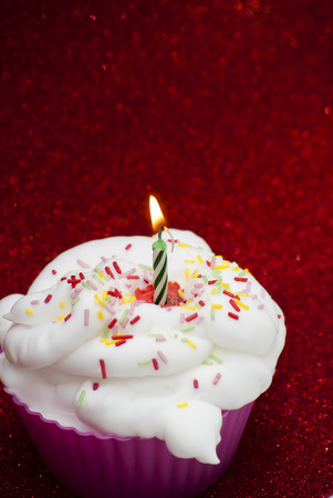christmas paste: Cupcake with a lit candle over bright red background Stock Photo