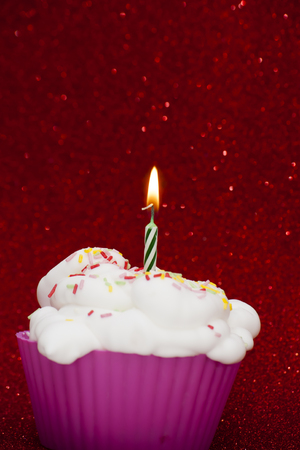 lit candle: Cupcake with a lit candle over bright red background Stock Photo