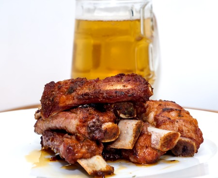 Roasted pork ribs on a white plate with a pitcher of beer next